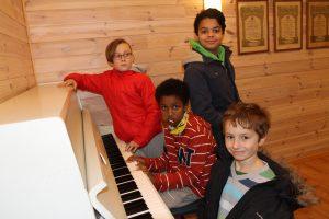 – Vi blir sultne av å spille innebandy, så da er det bra at det er mat etterpå, sier barna som tar plass ved pianoet.